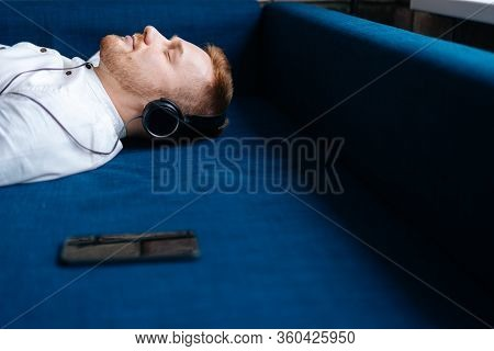 Young Handsome Man Listening To Relaxing Music, Lying On The Couch. Pleasant Music, Relaxation. Conc