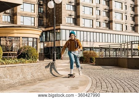 Young Handsome Woman Riding On A Skateboard. Portrait Of Sport Female Model In Urban Style. Skateboa