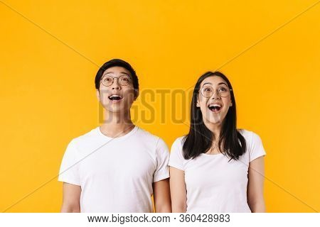 Image of excited multinational man and woman in eyeglasses looking upward isolated over yellow background