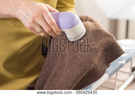 The Woman Holds An Electric Shaver In Her Hand To Clean Mottled Clothes And Cleans The Sleeve Of A B
