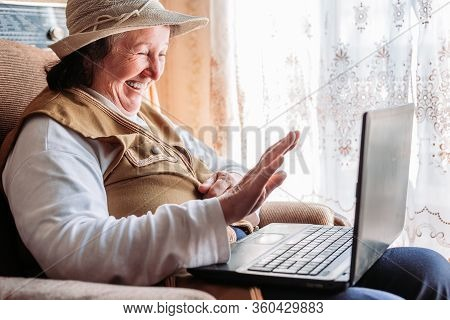 Elderly Woman Having A Video Call With Her Family, Smiling And Waving. Quarantine Time