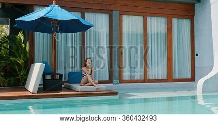 Woman sit at the swimming pool side and enjoy sunbath