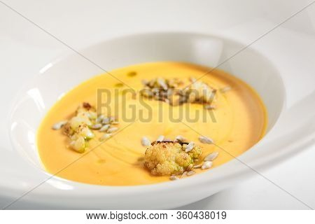 Pumpkin soup in white bowl. Served main course close up. Vegetable cream soup decorated with seeds. Restaurant food portion, main course. Vegetarian supper. Dinner, gourmet meal in plate