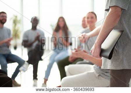 blurred image of a group of young people sitting in a circle