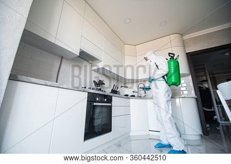 Coronavirus Pandemic. A Disinfector In A Protective Suit And Mask Sprays Disinfectants In House. Pro