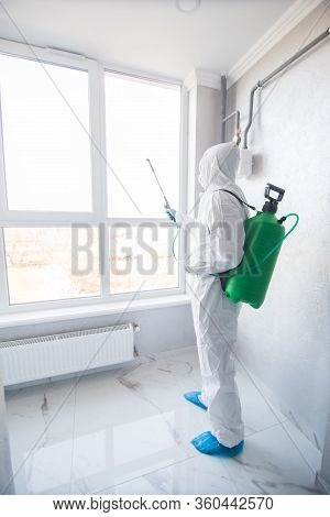 Disinfector In A Protective Suit Conducts Disinfection In Contaminated Area. Professional Disinfecti