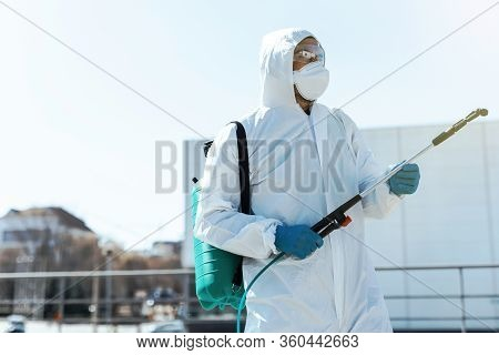 Disinfector In Protective Suit Conducts Disinfection In Contaminated Area Of Car To Prevent Coronavi