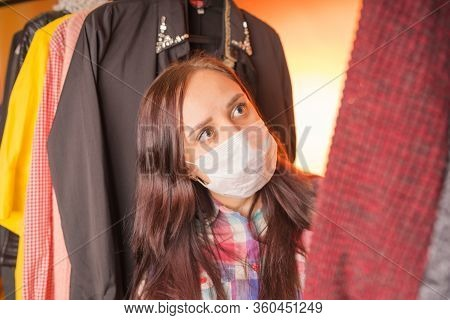 Close Up Of Young Woman In Medical Mask Looking Around, Pondering What To Choose Clothes In Wardrobe