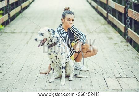 Man's Best Friend. Woman With Dalmatian Dog On The Bridge Posing.