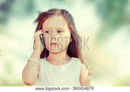 Kids & Technology Concept. Closeup Portrait Of Beautiful Serious Little Girl  Talking Mobile Having
