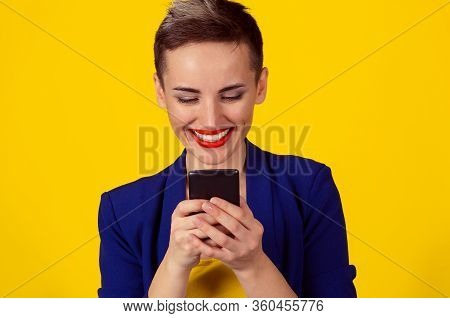 Staying Connected. Happy Young Woman Looking At Her Mobile Phone And Smiling Pumping Fist Celebrates