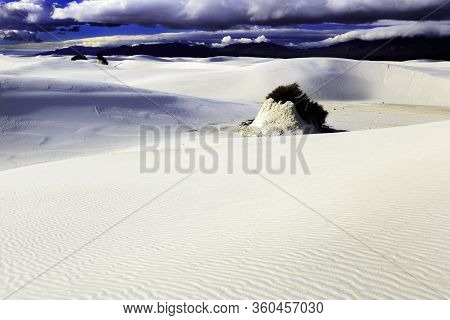 A Wind Eroded Pinnacle Capped By A Creosote Bush Amid The White Sand Dunes And Blue Skies At White S