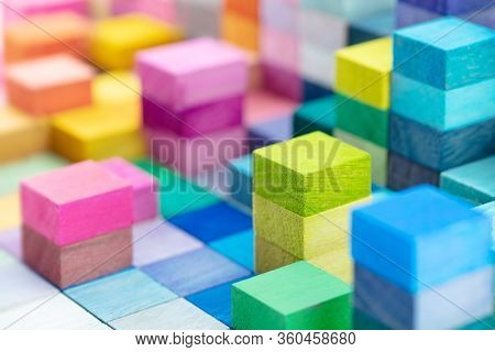 Spectrum of stacked multi-colored wooden blocks. Background or cover for something creative, diverse, expanding,  rising or growing. Shallow depth of field.