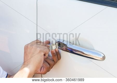 Close-up Of Person's Young Man Locksmith Hand Opening White Car Door With Lock Picker.