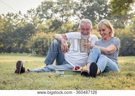 Elderly Couple Is Sitting On A Tablet In The Park.
