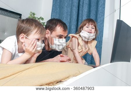 Cute Children Boy And Girl And Their Father In Medical Mask Sitting At Home In Quarantine. Entertain