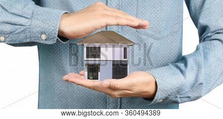 Mortgage Concept By Money House. Holding  House Model In Hand