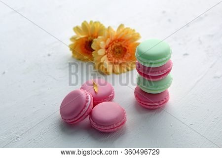 A French Sweet Delicacy, Colorful Macaroons Variety Closeup With Flowers On White Backround. Tasty M