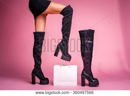 The Girl Stands With Her Foot Lifted Up In Black Jackboots Boots On Her Feet On A Pink Background. I