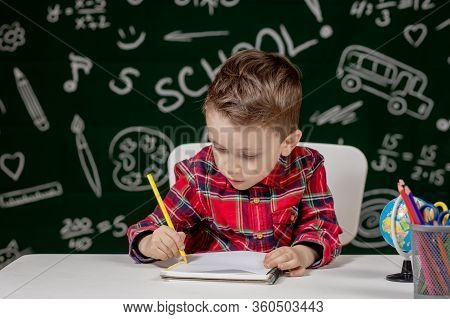Cute Child Boy Doing Homework. Clever Kid Drawing At Desk. Schoolboy. Elementary School Student Draw