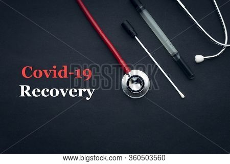 Covid-19 Or Coronavirus Recovery Text With Stethoscope And Medical Swab Black Background. Covid-19 O
