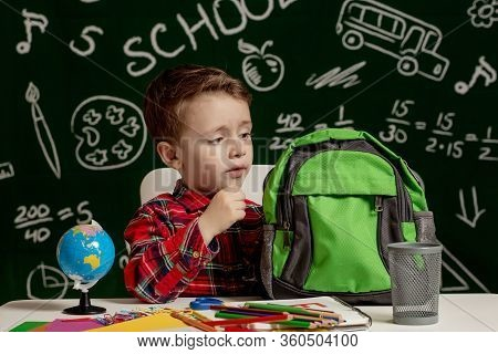 First Day Of School. Kid Boy From Primary School. Back To School. Little Boy Collects School Backpac