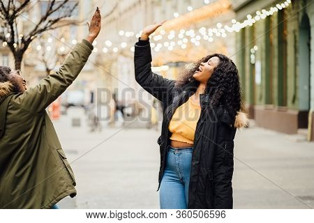 Happy Exuberant Young Girl Friends Giving A High Five Slapping Each Others Hand In Congratulations A
