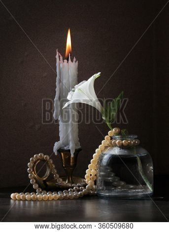 Retro Style Still Life With Alstroemeria Flower In The Small Vintage Bottle, Candlestick With Burnin
