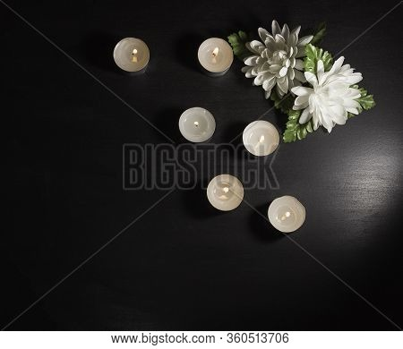 Funeral Symbol. Two White Flowers And Burning Candles On A Black Background. Free Space For Text, To