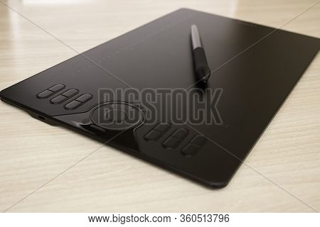 Graphic Tablet And Stylus With Stylus Stand On The Table. Side View, Tools For Graphic Drawing.
