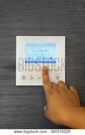 African Female Hands On The Air Conditioning Control Panel. Hand Girl Setting Temperature Air Condit