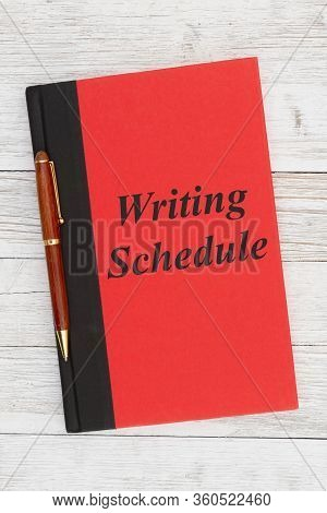 Writing Schedule Message On A Red Book With Pen On Weathered Whitewash Wood