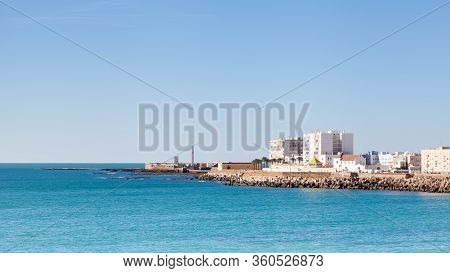 Cadiz Waterfront.  The Cadiz Waterfront In Spain With The Castillo De San Sebastian In The Backgroun