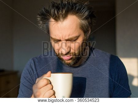 Close Up Funny Man After Awakening Looking At His A Big Cup Of Coffee Or Tea.
