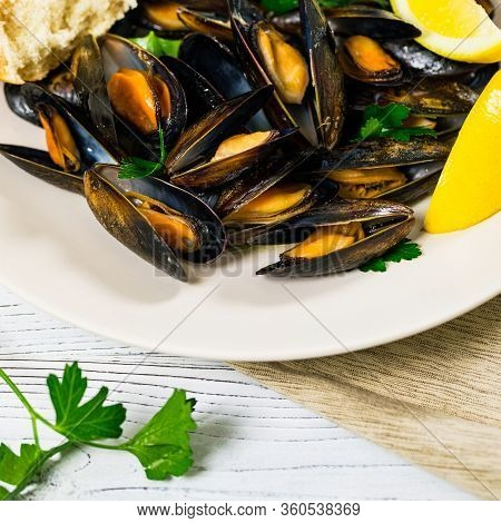 Delicious Seafood Mussels With Lemon And Parsley. Clams In The Shells On Wooden Background. Selectiv