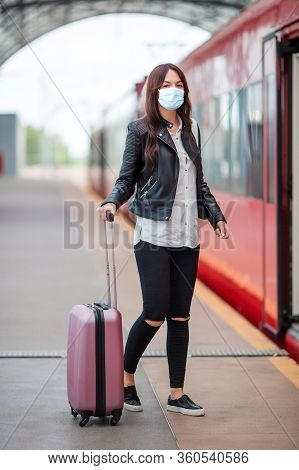 Young Tourist Woman With Baggage On The Platform Waiting For Train
