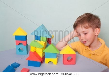 Child A Boy In A Yellow Polo Shirt Builds A House From A Color Constructor, Isolate On A Blue Backgr