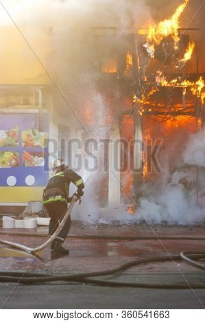 Firefighter Extinguishes A Fire In A Burning Building With Water From A Hose. Hazardous Work Fireman