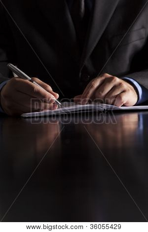 Businessman Writes In Notebook