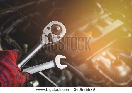 Hand Of Mechanic Professional Man Hold A Wrench Tools With Car Engine Blurred Background In Vehicle