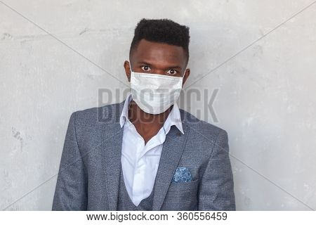 Covid-19. Confident Young African Man Is Wearing A Protective Medical Face Mask To Prevent Infection