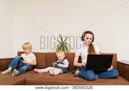 Young Mother With Computer In Hand And Kids With Phones Sitting On Couch. Overuse Of Devices.