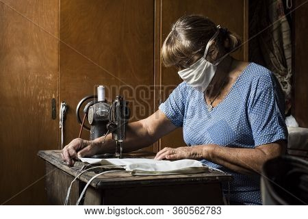 Grandmother In Quarantine Making Masks Or Chinstrap With Her Old Sewing Machine Being In Solidarity
