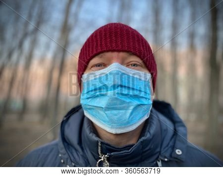 Portrait of man wearing protective respirator face mask outdoor during covid-19 coronavirus pandemic virus quarantine.