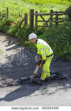 Buckingham, Uk - May 03, 2018. Man Wearing High Visibility Clothing Repairing Potholes In Damaged Ro
