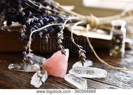 A Side View Image Of Rose Quartz And Clear Quartz Crystal With Dried Lavender And Old Book.