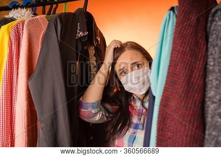 Close Up Of Young Woman In Medical Mask Standing Between Clothes In Wardrobe And Scratching Head, Po