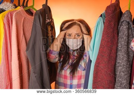 Close Up Of Young Woman In Medical Mask Standing Between Clothes In Wardrobe And Grabbing Head, Pond