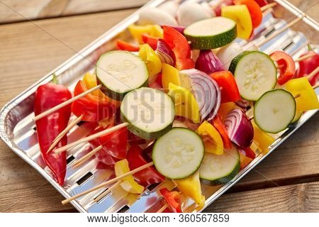 cooking, barbecue and food concept - close up of vegetables with champignons on skewers stacked on disposable foil grill on wooden table