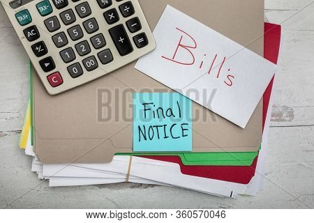 Bills Final Notice Sign Posted On A Office File Folder Full Of Bills And Payments With Calcultor Fla